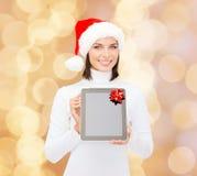 Mujer en sombrero del ayudante de santa con PC de la tableta Fotos de archivo libres de regalías