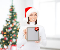 Mujer en sombrero del ayudante de santa con PC de la tableta Imagen de archivo libre de regalías