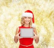 Mujer en sombrero del ayudante de santa con PC de la tableta Fotos de archivo