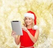 Mujer en sombrero del ayudante de santa con PC de la tableta Foto de archivo libre de regalías