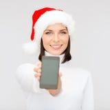 Mujer en sombrero del ayudante de santa con smartphone Imagen de archivo