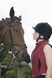 Mujer en sombrero del montar a caballo con el caballo al aire libre Imagen de archivo libre de regalías