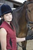 Mujer en sombrero del montar a caballo con el caballo al aire libre Foto de archivo