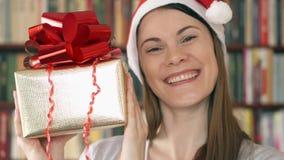 Mujer en sombrero del ` s de Papá Noel con el presente Hembra con la caja de regalo de oro con la cinta roja que celebra la Navid metrajes