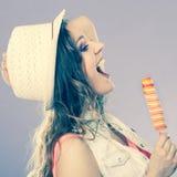 Mujer en sombrero del verano que come la crema del estallido del hielo Fotos de archivo