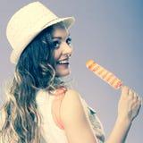 Mujer en sombrero del verano que come la crema del estallido del hielo Foto de archivo libre de regalías