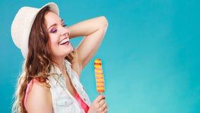 Mujer en sombrero del verano que come la crema del estallido del hielo Imágenes de archivo libres de regalías