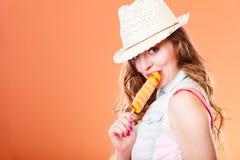 Mujer en sombrero del verano que come la crema del estallido del hielo Foto de archivo