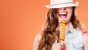 Mujer en sombrero del verano que come la crema del estallido del hielo Imagen de archivo