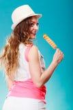 Mujer en sombrero del verano que come la crema del estallido del hielo Fotografía de archivo