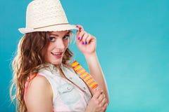 Mujer en sombrero del verano que come la crema del estallido del hielo Fotografía de archivo libre de regalías