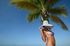 Mujer en sombrero del verano que toma el sol bajo una palmera en un fondo Fotos de archivo libres de regalías