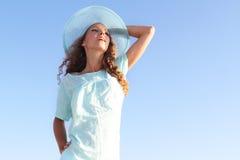 Mujer en sombrero del verano sobre fondo del cielo Foto de archivo libre de regalías