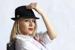 Mujer en sombrero en la silla aislada en el fondo blanco Fotos de archivo libres de regalías