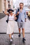 Mujer en sombrero que camina abajo de la calle con el hombre Foto de archivo