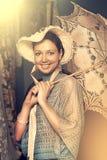 Mujer en sombrero viejo con un paraguas del cordón Foto de archivo