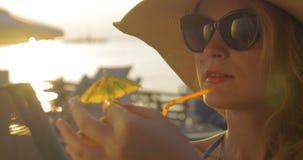 Mujer en sombrero y gafas de sol que bebe el cóctel almacen de video