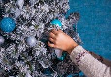 Mujer en suéter que adorna el árbol de navidad con las bolas en fondo azul Foto de archivo libre de regalías