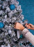 Mujer en suéter que adorna el árbol de navidad con las bolas en fondo azul Fotos de archivo