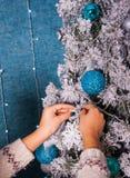 Mujer en suéter que adorna el árbol de navidad con las bolas en fondo azul Imagen de archivo