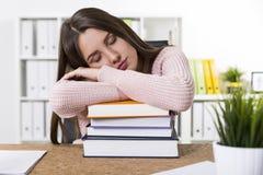 Mujer en suéter rosado que duerme en la pila de libros imágenes de archivo libres de regalías