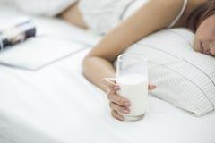 Mujer en su cama con un vidrio de la leche a disposición, de la profundidad y del foco bajo sobre el vidrio de leche Fotos de archivo libres de regalías