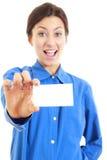 Mujer en su 20s en la camisa azul que muestra la tarjeta de visita en blanco Imágenes de archivo libres de regalías