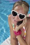 Mujer en su teléfono celular por la piscina Fotografía de archivo