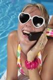 Mujer en su teléfono celular por la piscina Imágenes de archivo libres de regalías