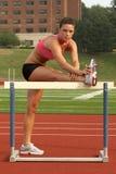 Mujer en sujetador de los deportes y cortocircuitos que estiran el tendón de la corva en cañizo Imagenes de archivo
