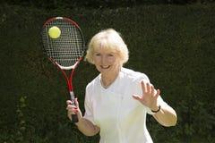 Mujer en sus años 60 que juegan a tenis Fotografía de archivo libre de regalías