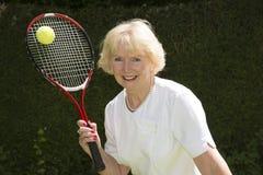 Mujer en sus años 60 que juegan a tenis Foto de archivo
