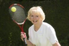 Mujer en sus años 60 que juegan a tenis Imágenes de archivo libres de regalías