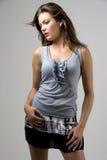 Mujer en tapa gris y falda corta Imagen de archivo