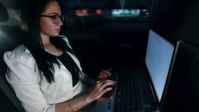 Mujer en taxi - la mujer trabaja en un ordenador portátil en el coche en la noche almacen de metraje de vídeo