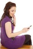 Mujer en teléfono de la sonrisa boba de la parte posterior de la púrpura Fotos de archivo libres de regalías