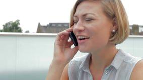 Mujer en terraza del tejado usando la tableta de Digitaces y el teléfono móvil almacen de video