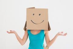 Mujer en top sin mangas azul con la caja de cartón sonriente sobre cara Fotos de archivo