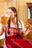 mujer en Tracht bávaro en restaurante o pub Fotos de archivo libres de regalías