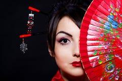 Mujer en traje asiático con el ventilador asiático rojo Foto de archivo