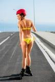 Mujer en traje de baño con los rodillos en la carretera fotografía de archivo libre de regalías