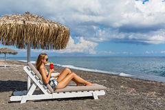 Mujer en traje de baño en la playa con un cóctel Foto de archivo libre de regalías