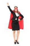 Mujer en traje del super héroe con el puño aumentado Imágenes de archivo libres de regalías