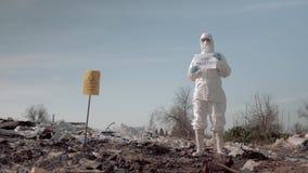 Mujer en traje protector y cartel de la tenencia de la máscara con lema de la contaminación de la parada en la descarga de basura almacen de video