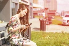 Mujer en un banco de la ciudad con un smartphone Imagenes de archivo