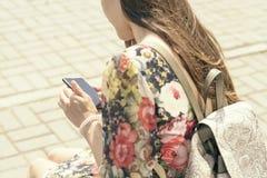 Mujer en un banco de la ciudad con un smartphone Imagen de archivo libre de regalías