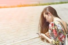 Mujer en un banco de la ciudad con un smartphone Imágenes de archivo libres de regalías