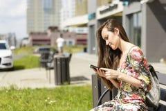 Mujer en un banco de la ciudad con un smartphone Fotos de archivo libres de regalías