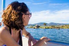 Mujer en un barco que mira hacia fuera al mar Foto de archivo libre de regalías