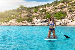 Mujer en un bikini en un soporte encima del tablero de paleta sobre la turquesa, aguas mediterráneas imagen de archivo